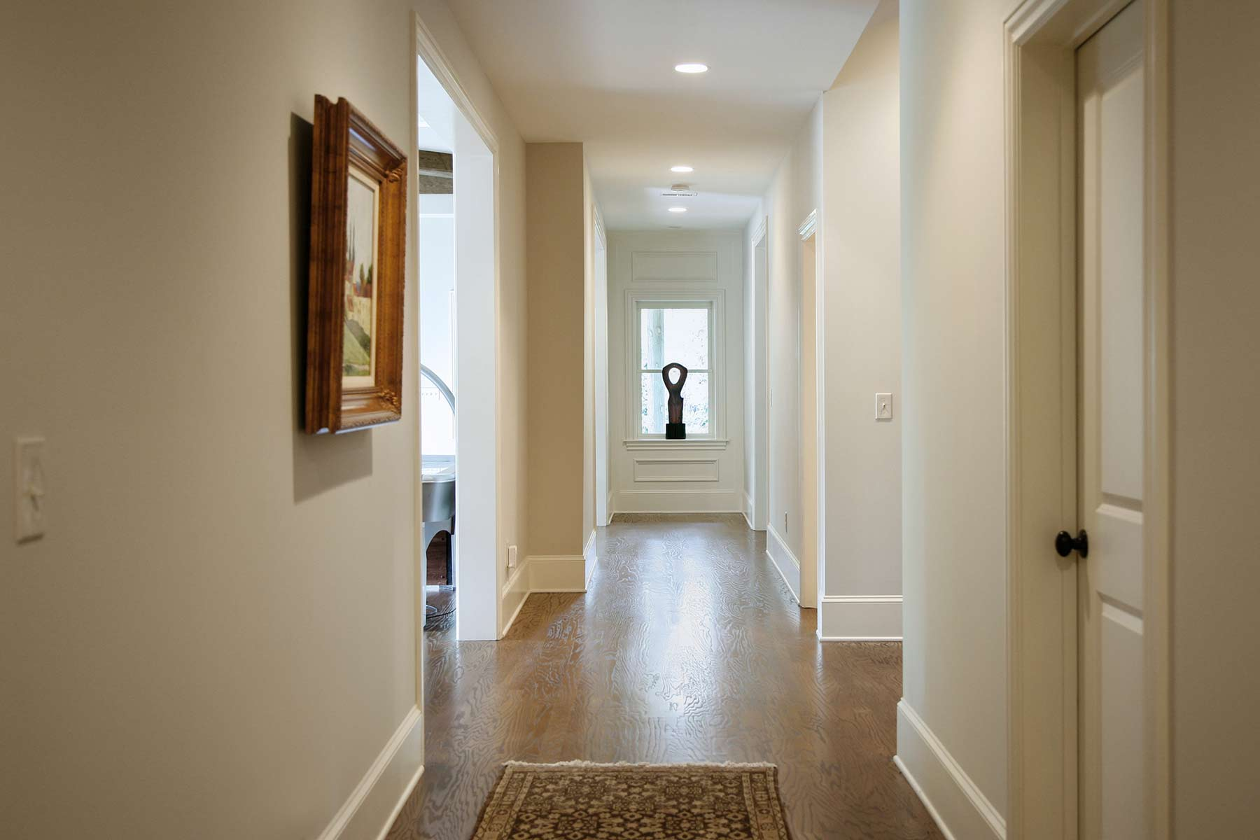 Finished basement hallway with recessed lighting