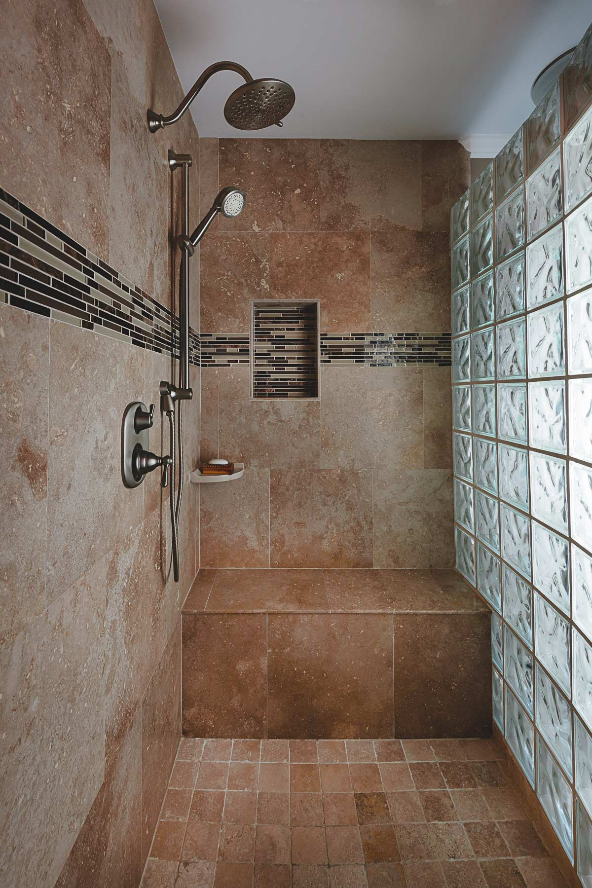 Beautiful walk-in shower with custom tile and built-in shower seat