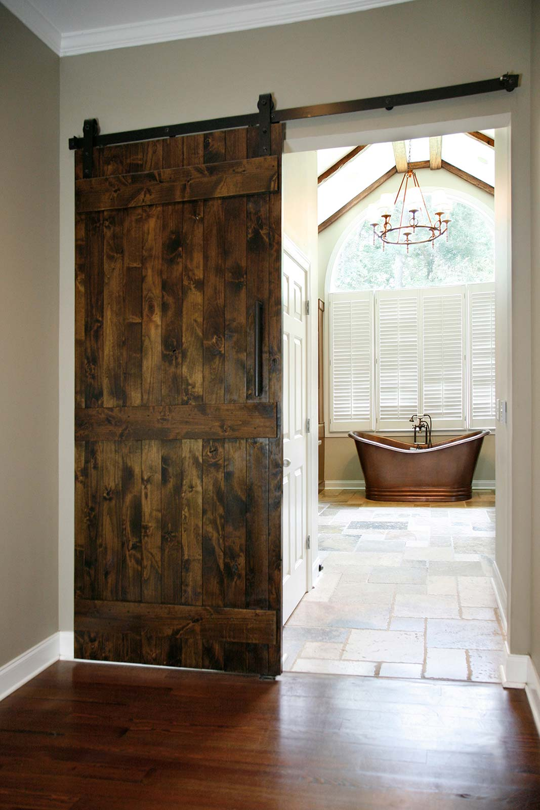 Closer view of barndoor style doors leading to bathroom