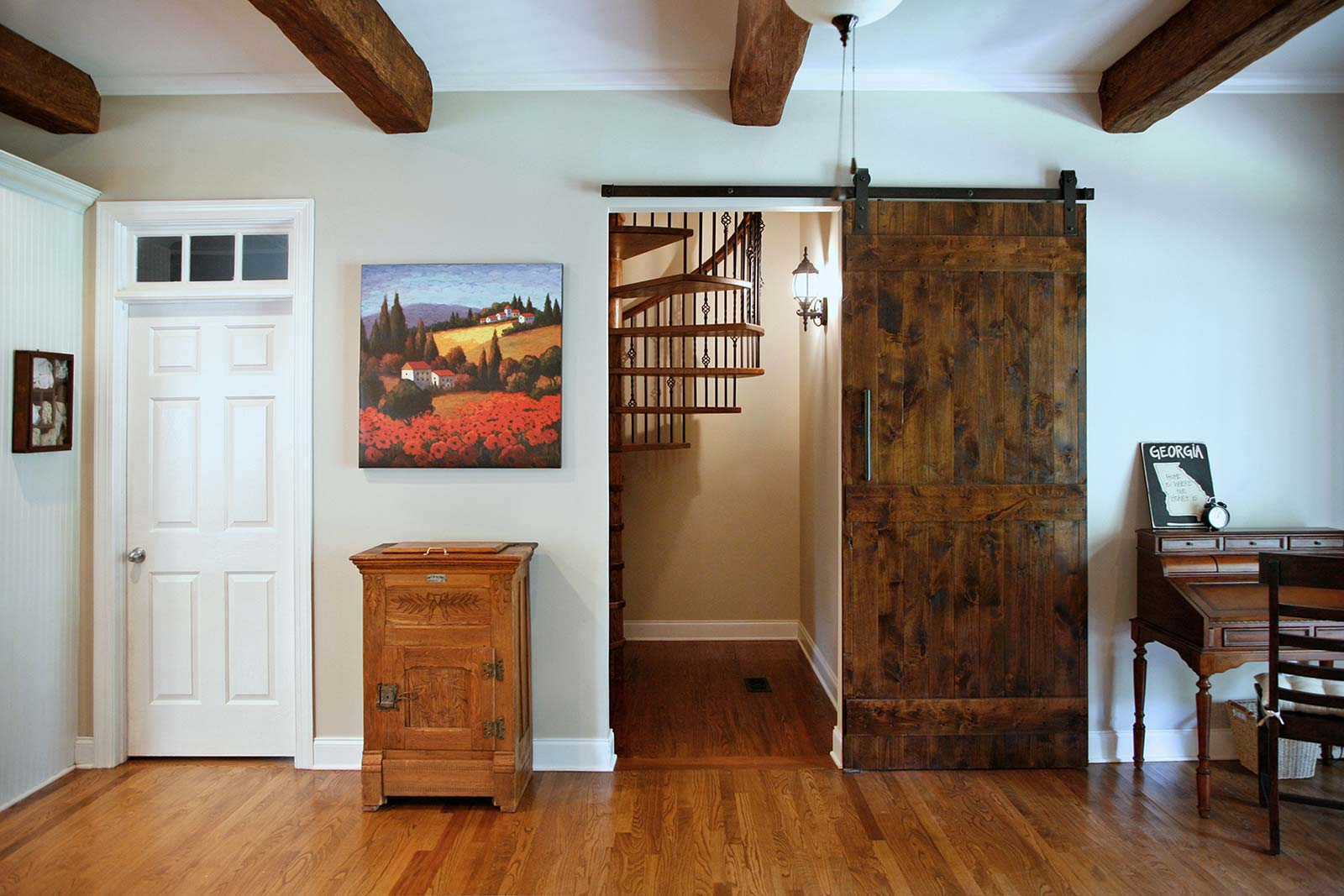 Barndoor style door conceals spiral stairs