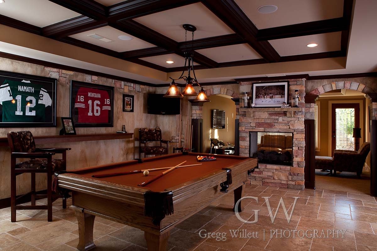 Remodeled basement with coffered ceiling, stone fireplace, and pool table