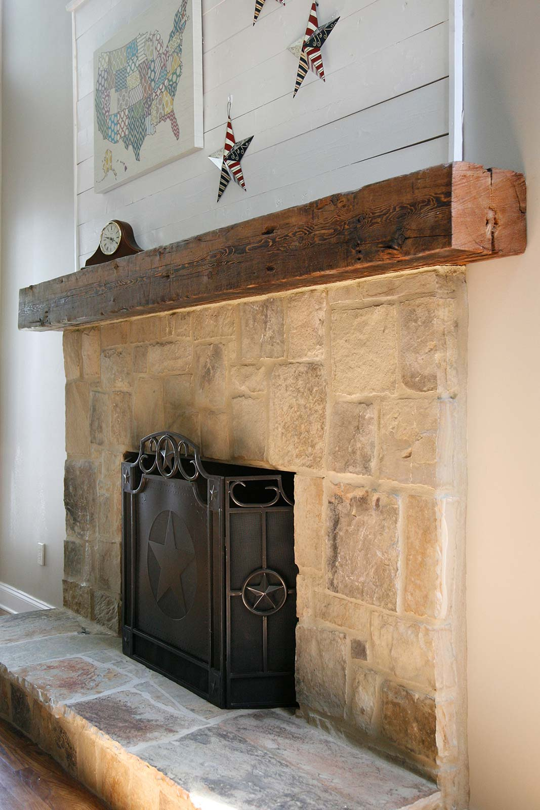 Large timber mantle over cut stone fireplace surround