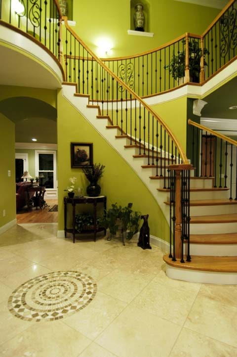 Dramatic entryway with curved stairs, custom railing and a balcony