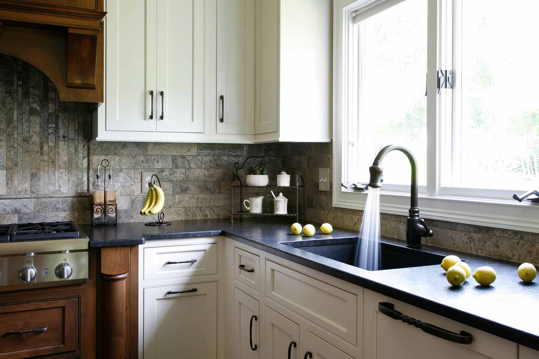 Newly remodeled kitchen boasts natural wood, white cabinets, and dark solid surface countertop
