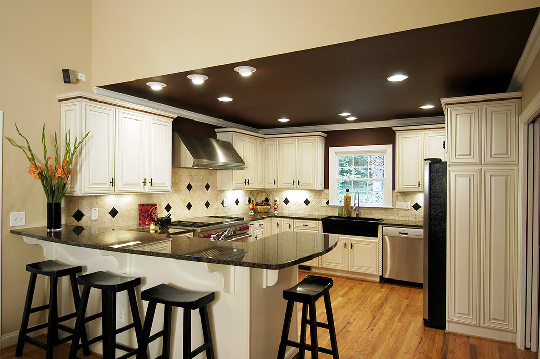 High-contrast kitchen remodel with light cabinets, dark counters and a dark ceiling with recessed lights