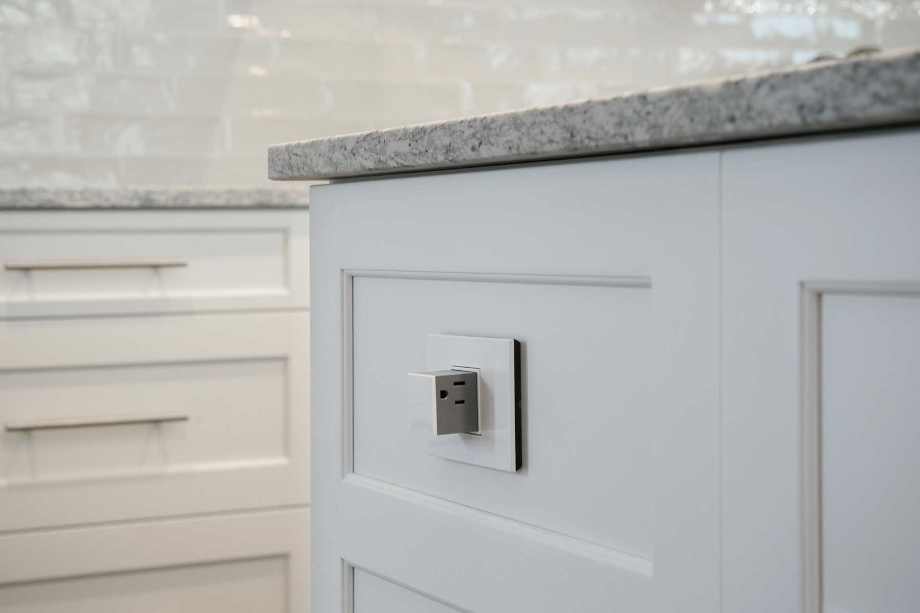 Hidden push/pop-out electrical outlet in kitchen island