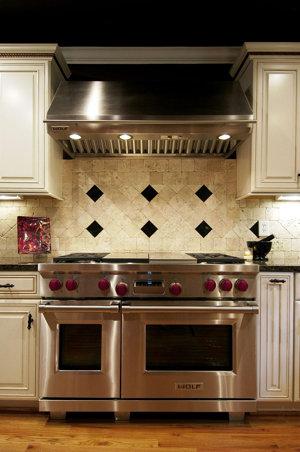 View of stovetop with custom tile backsplash in black and white